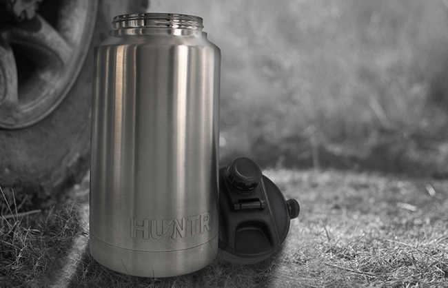 Lifestyle image HUNTR water bottle beside car tire