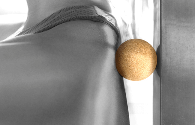 Lifestyle image of woman using a cork roller ball for back muscles