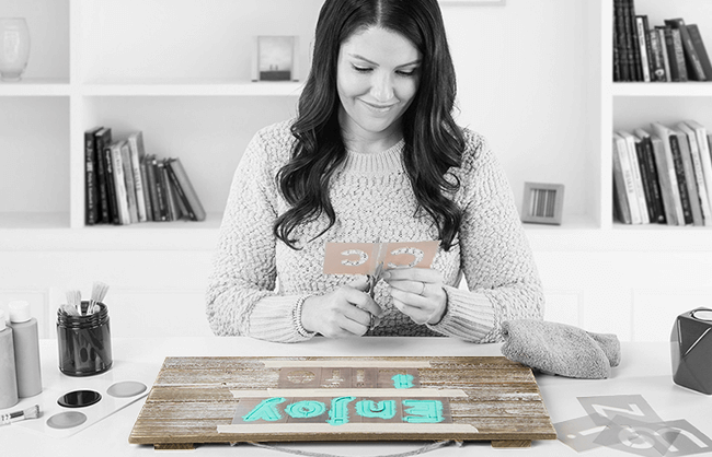 Lifestyle image of female model doing crafts at home