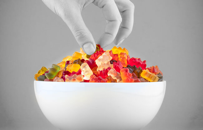 Woman picking up candy out of a bowl