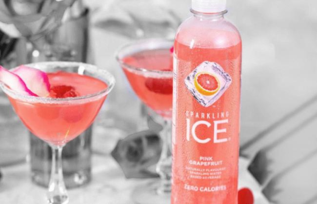 Sparkling ice bottle beside cocktails