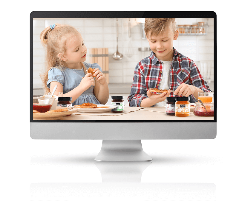 Lifestyle image of kids spreading jam on their toast in a bright kitchen in the morning displayed on a large Mac monitor
