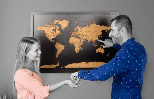 Lifestyle image of a couple placing pins on their travel map