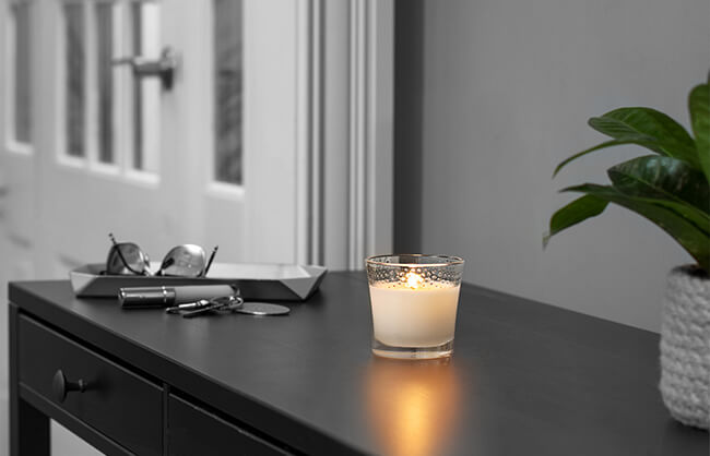 Candle lit on entry way table of home