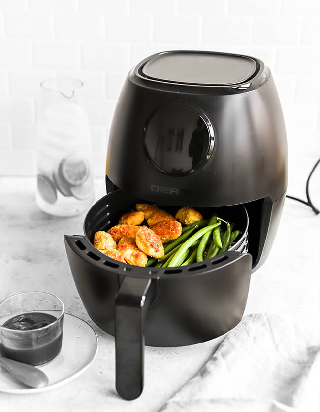 Lifestyle image of air fryer in kitchen with cooked food in drawer