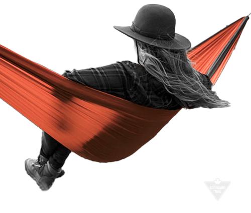 Woman in hat sitting in hammock facing away