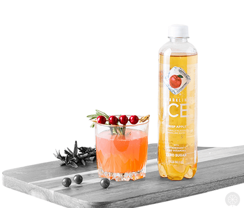 Lifestyle image of sparkling ice bottle beside a cocktail on a cutting board