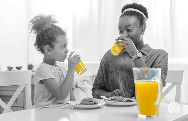 Mother and daughter drinking orange juice in the morning