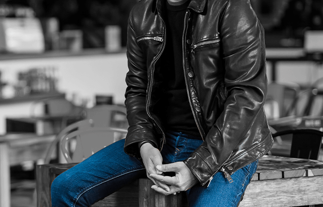 Man sitting on edge of table wearing a leather jacket
